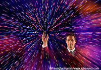 A businessman holds up a cell phone emitting or receiving a colorful flow of signals, information and data symbolizing communications technolgoy.